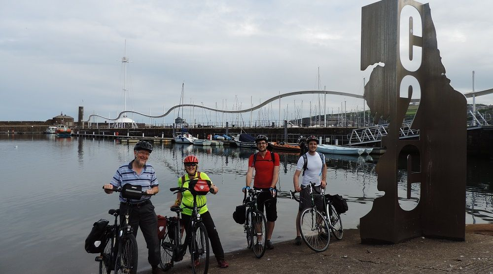 Four cyclists at the start of the C2C, with the C2C sign behind them